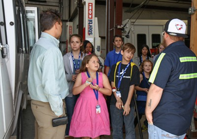 Kids get a tour of the TAPS garage area during the first annual Take Our Daughters and Sons to Work Day